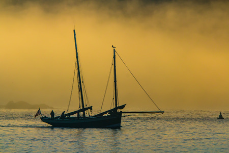 ketch: Ketch heading out to sea at sunrise on a misty day