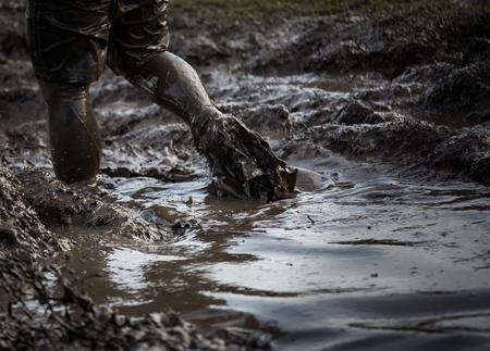 Diep modderig water met voeten die er doorheen spatten en de modder in een race slepen