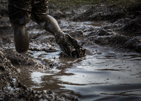 Tief schlammigem Wasser mit den Füßen durch Spritzwasser und Ziehen der Schlamm in einem Rennen