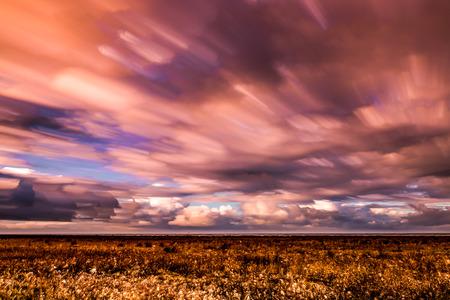timelapse: timelapse movement of clouds across marshland to the distant sea Stock Photo