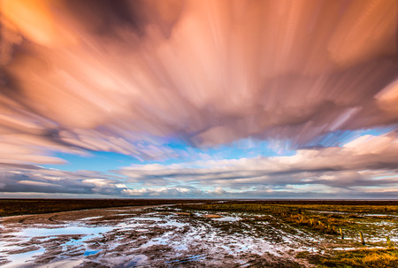 timelapse movement of clouds across marshland and water 版權商用圖片
