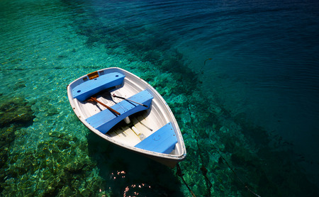 turquoise water: Small white boat on the tranquil turquoise water in tropics. Stock Photo