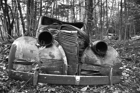 An abandoned coupe in black and white