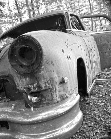 junk car: A bullet ridden car body in black and white