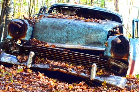 junk car: An abandoned car with autumn leaves Stock Photo