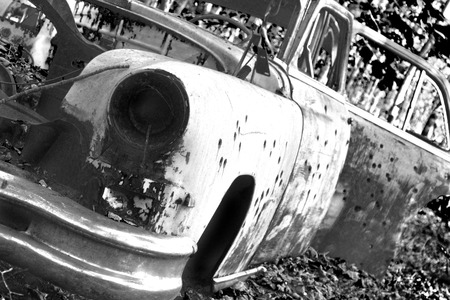 junk car: A bullet ridden sedan in black and white