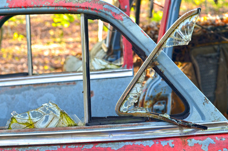 Glass is broken out of abandoned car windows