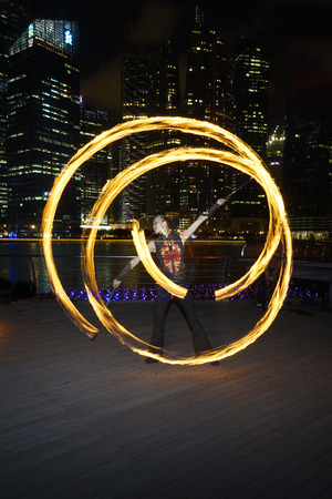 poi: SINGAPORE - MARCH 15, 2014  Fire Dancer street performance using fire poi, at Marina Bay