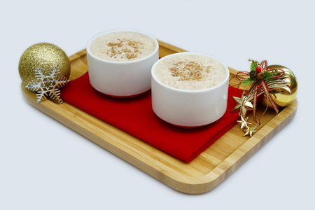 Traditional eggnog sprinkled with nutmeg for Christmas and winter holidays.