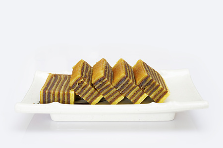 Multi-layered cake called lapis legit or spekkoek from Indonesia, isolated on white background.