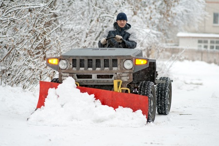 The man operates the snow-plow.Winter