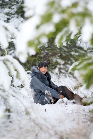 beautiful girl sits one in wood in the winter Stock Photo - 11764953