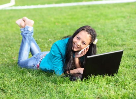young woman lying down using a laptop