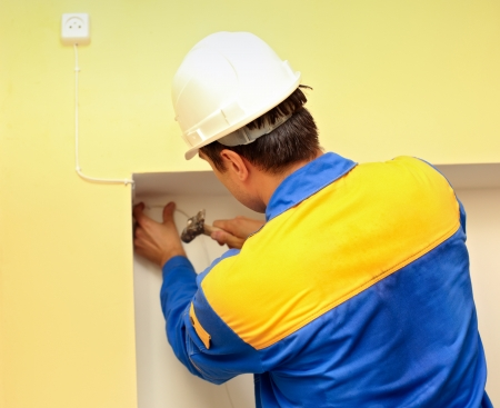 man electrician installs electrical network photo