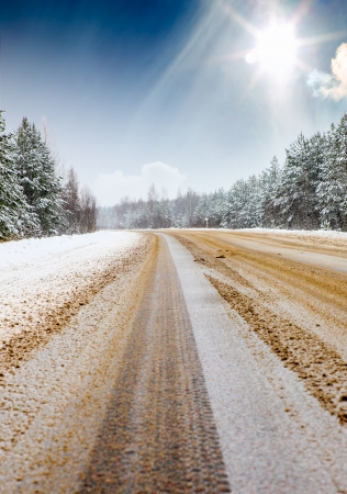 Dangerous snowy road in the forest photo