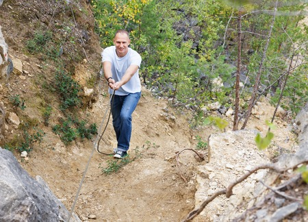 rockclimb: man up the hill holding a rope Stock Photo