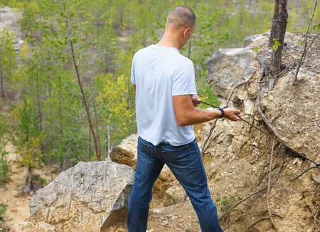 rockclimb: man holds the rope on the edge of a rocky cliff