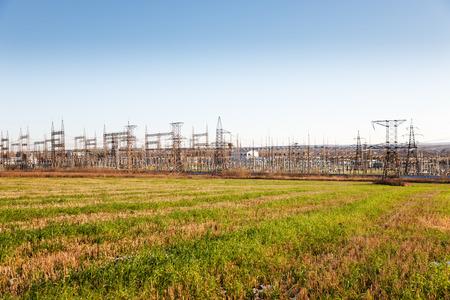 isolator high voltage: High voltage power transformer in substation  against  blue sky