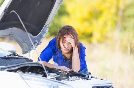 exasperation: sad girl with a broken car with open hood