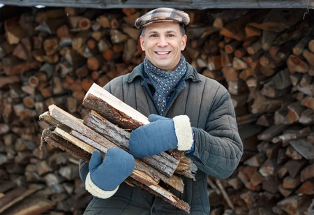 russian man: Man in Winter Clothes Carrying Firewood