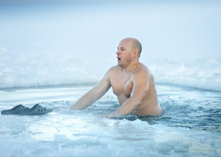 Winter swimming. Man in an ice-hole Stock Photo