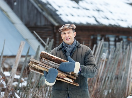 armful: man holding an armful of firewood in winter