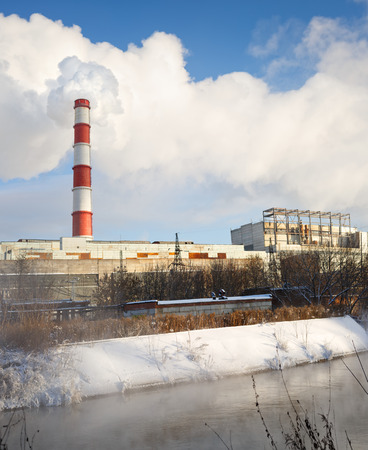 winter view of  thermal power plant  against cloudy blue sky