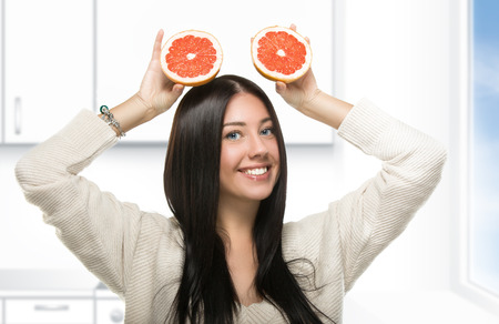funny brunette girl holding a citrus in the kitchen