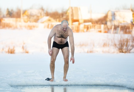 Winter-swimmer in ice-hole at lake in frosty day