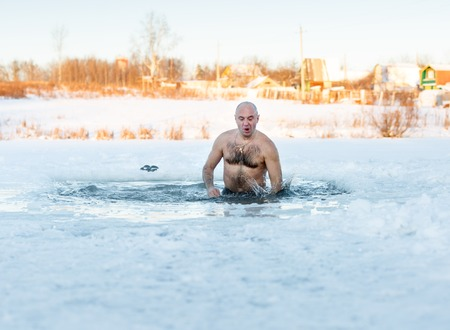 Winter swimming. Man in an ice-hole  in outdoors photo