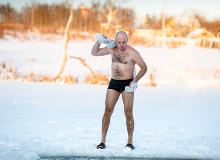 man  wipes towel on a cold day outdoors