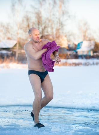 man wipes a towel after swimming in the water in winter photo