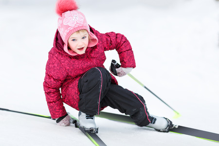 Little girl  going down from snowy hill Stock Photo