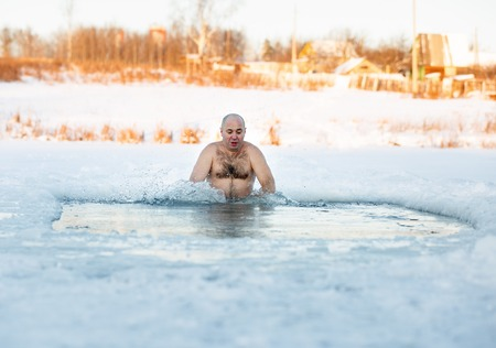 Winter swimming. Man in an ice-hole  in outdoors Stock Photo