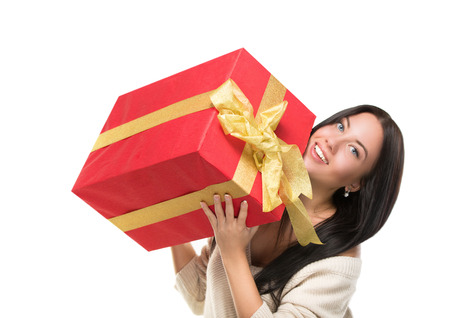 Portrait of casual young happy smiling woman hold red gift box. Isolated studio background female model. Stock Photo