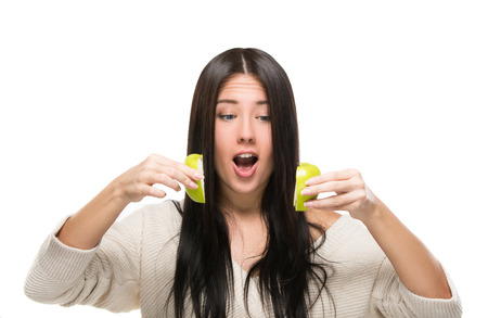 cut up: funny girl looks on cut up green apple Stock Photo