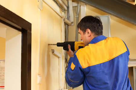 making hole: repair, building and home concept -  ma with electric drill making hole in wall