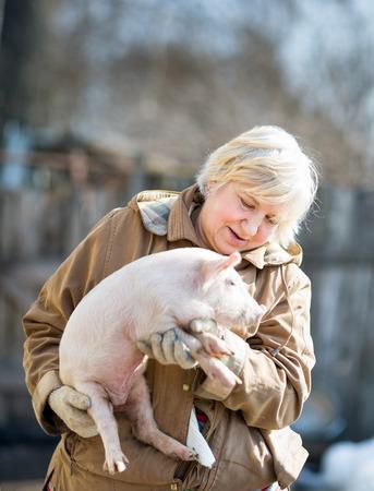 domestic animal: happy woman holding a newborn piglet,domestic animal breeding