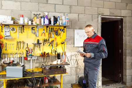 mechanician: Mechanic worker studying his instructions at a construction home studio Stock Photo