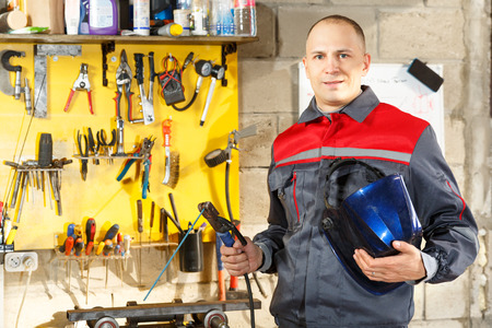 soldadura: trabajador con protector de metal de soldadura m�scara en el estudio casero de la construcci�n Foto de archivo