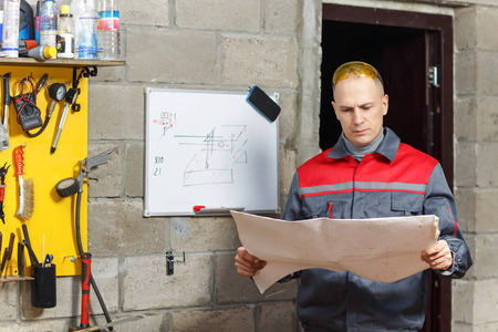 operative: Mechanic worker studying his instructions at a construction home studio Stock Photo