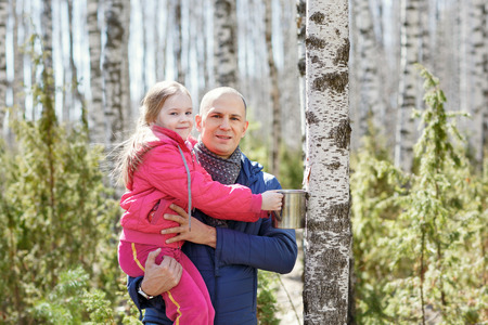 Father and daughter in the woods collect birch sap