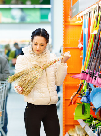 purge: Woman chooses a broom. Beauty Woman in Shopping Mall. Stock Photo