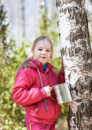sylvan: happy child collects birch sap in spring forest
