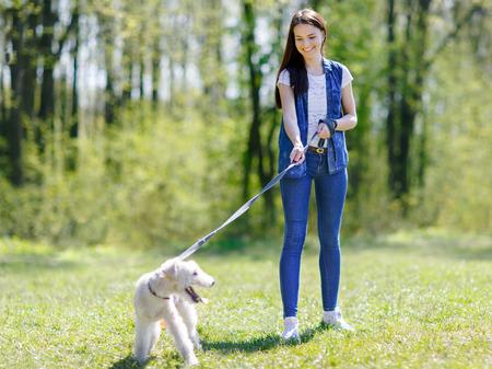 mujer con perro: Muchacha que recorre con un perro con una correa en un parque de verano