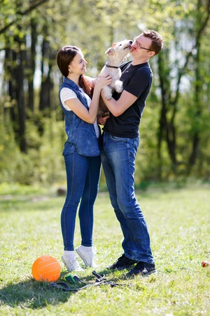 guardianship: couple and dog licking his owner in face as a sign of affection