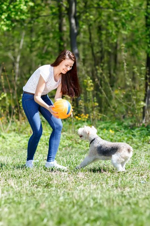 girl in motion Ball trains the dog in a summer park