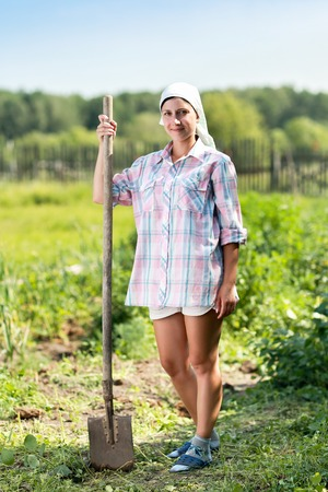 garth: woman with  spade in  garden among beds Stock Photo