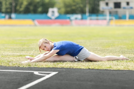 Pretty woman doing exercises at a stadium sitting on the splits .Fitness sport model training outside.