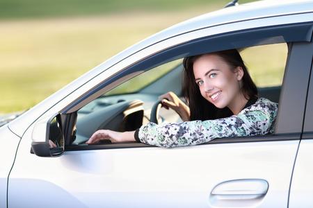 chofer: Hembra joven feliz por conducir su coche o controladores de nueva licencia